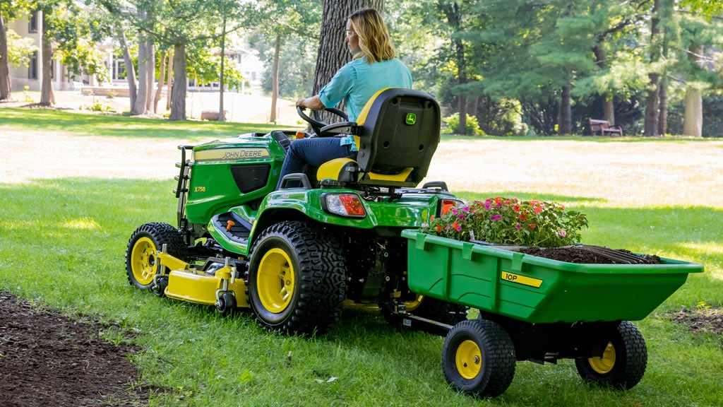 woman driving mower with cart attachment driving away