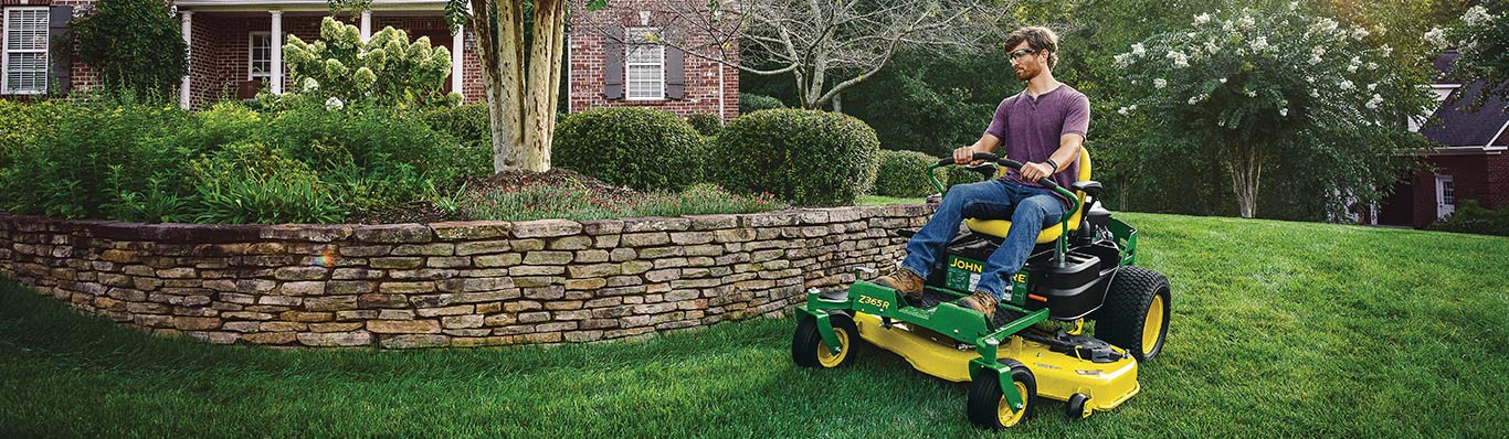 man driving z300 lawn tractor in yard
