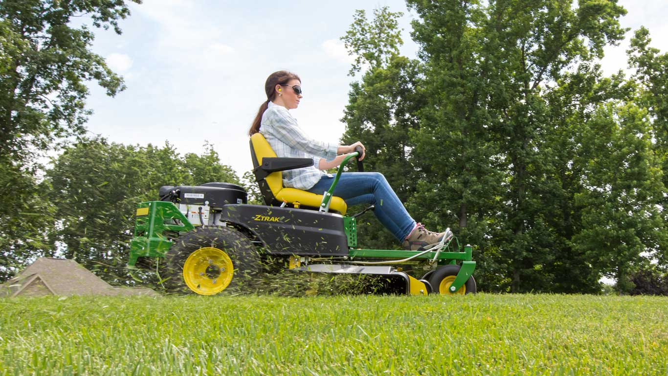 low view of woman on Z300 with grass clippings flying out of mower