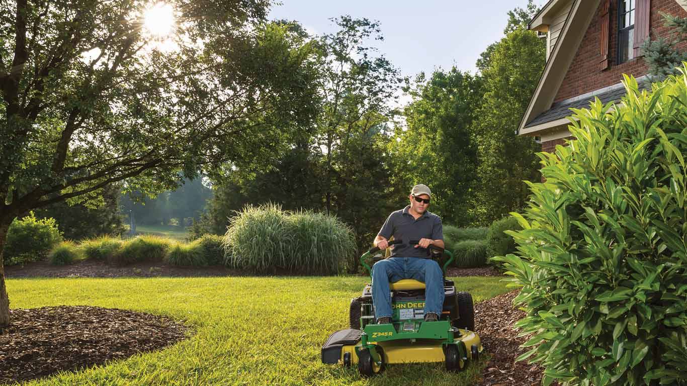man on Z300 cutting lawn near large hedge