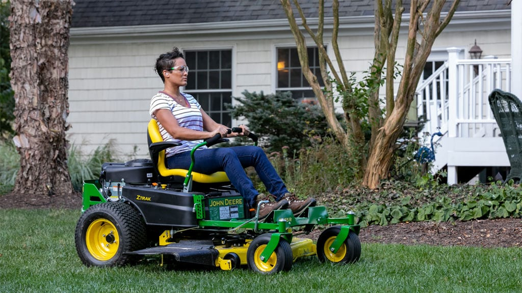 woman driving Z300 series mower in her yard