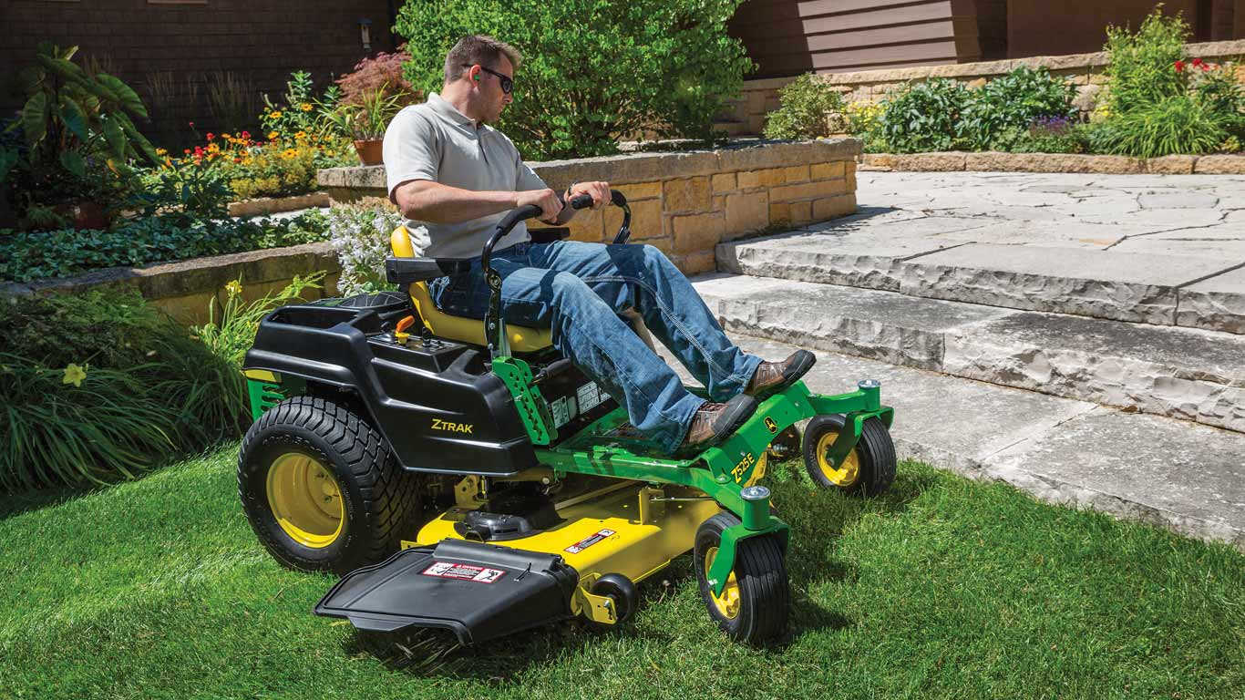 man on a Z500 ZTrak cutting lawn near stone steps