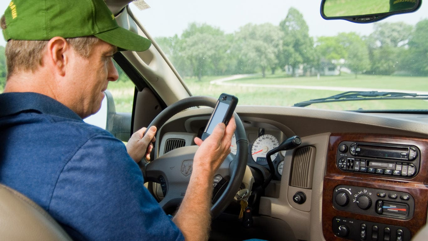 image of man in truck looking at mobile device