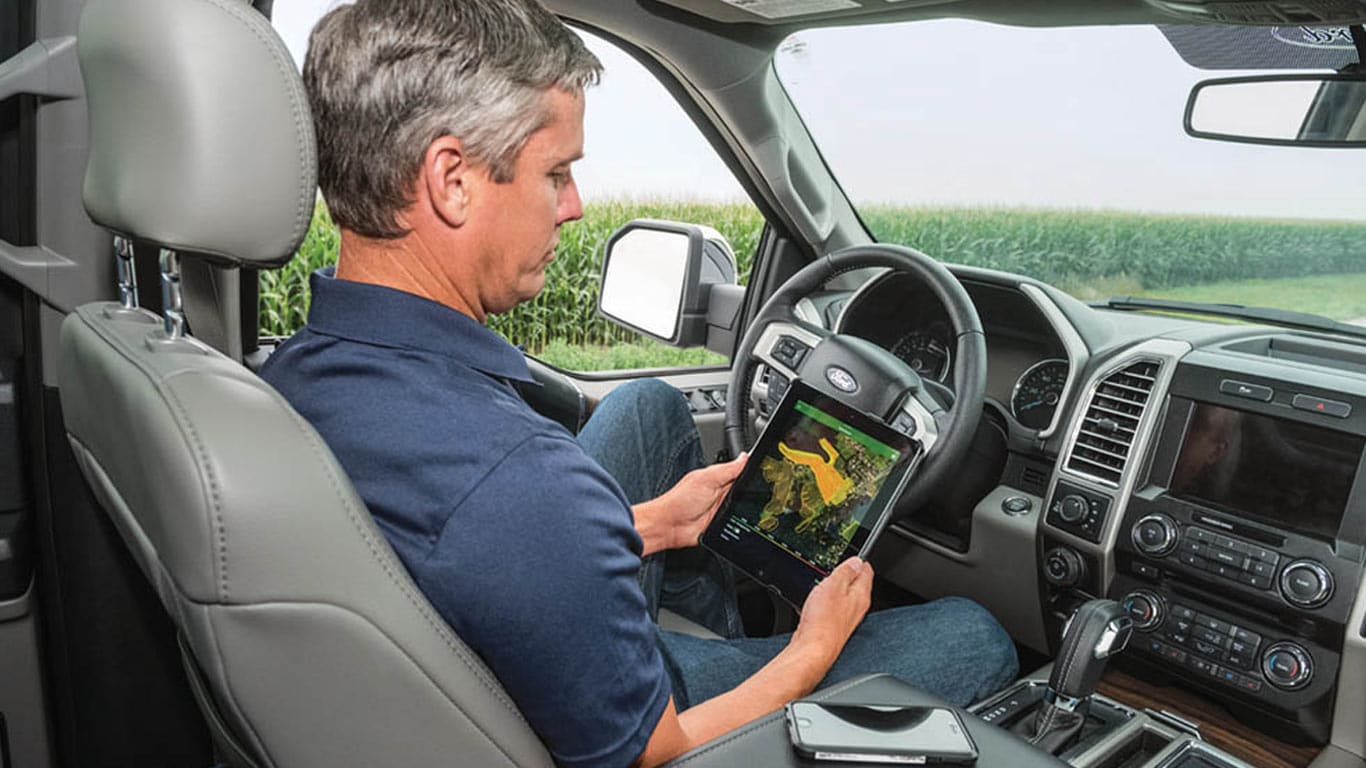 man in truck looking over data