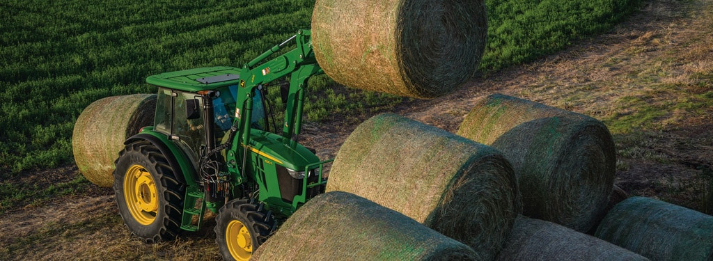 aerial view of a tractor loaded rolls of hay