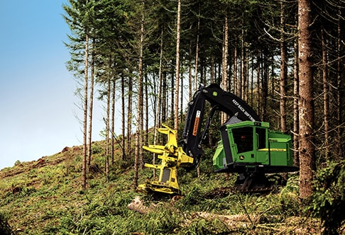 John Deere Feller Buncher with FR24B Felling Head chopping down a tree at the edge of a forest with blue sky in the background