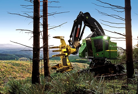 John Deere Feller Buncher with FR24B Felling Head working in a forest with mountains in the background