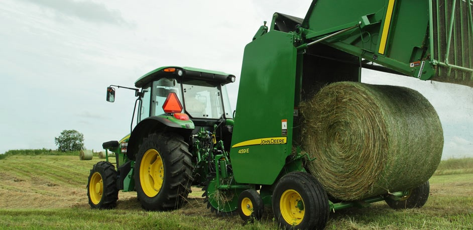 tractor unloading a bale