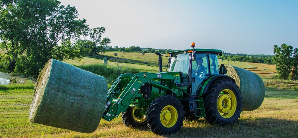Tractor moving bale