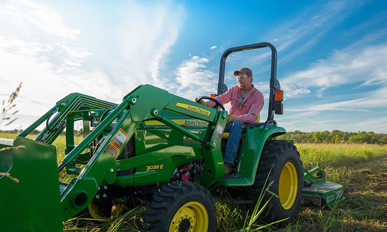 Image of man on E Series tractor in the field