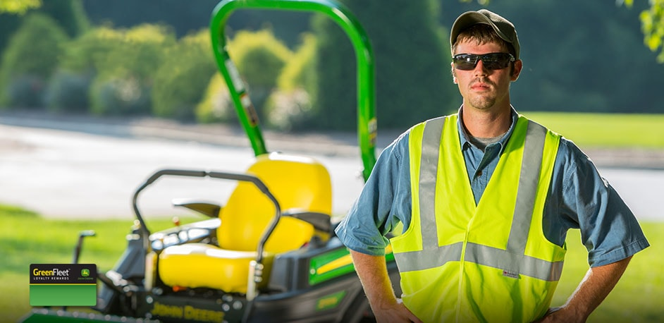 Photo of  a landscaper with a John Deere ZTrak in the background.