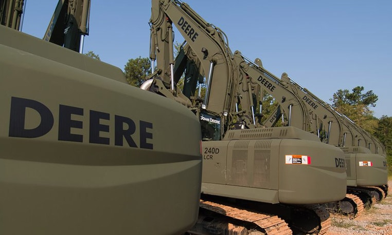 Line of John Deere excavators in military colors