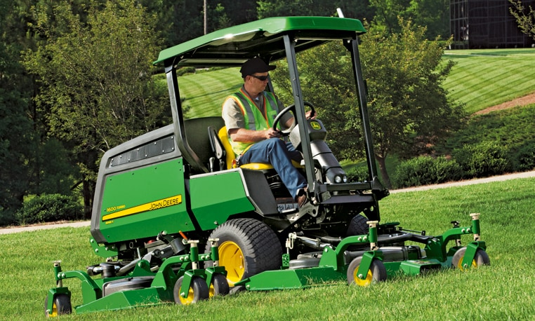Individual operating a riding mower on a hill