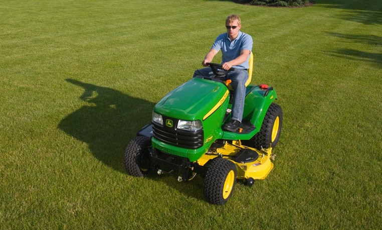 Man driving a mower on a lawn