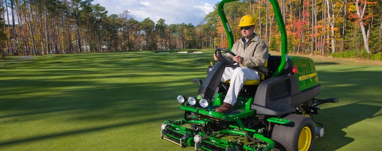 Worker mows golf course