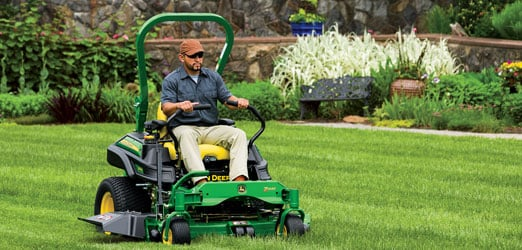 A worker using a John Deere commercial mower on a grassy lawn