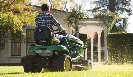 Man mows lawn with riding mower