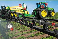 A John Deere tractor works in a field pulling attachments