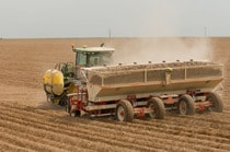 John Deere tractor with fertilizing implement working in a dusty field