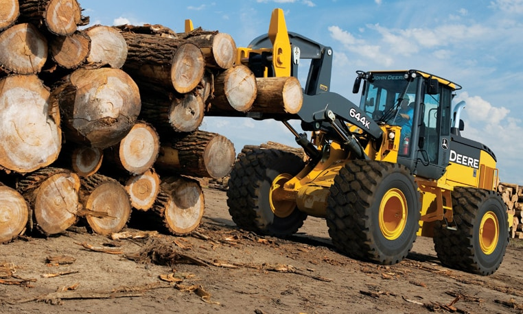 John Deere loader with log fork attachment piling up logs