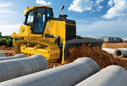 right hand view of the 700k dozer pushing dirt next to concrete drainage pipes