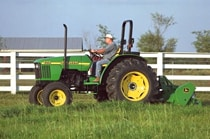 Man using a John Deere tractor with attached 360 Flail Mower to cut grass next to a white fence