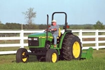 Man using a John Deere tractor with attached 390 Offset Flail Mower to cut grass next to a white fence