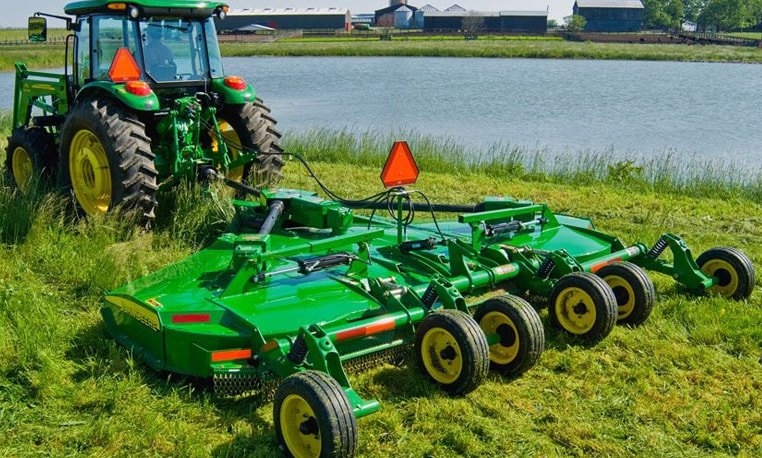 John Deere tractor with rotary cutter attachment trimming grass near a pond