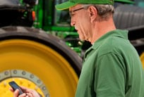 Farmer looking at his mobile phone with a John Deere tractor in the background