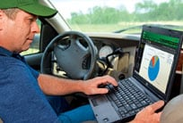 Farmer working on a laptop while parked in his truck