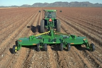 Rear view of a John Deere tractor with CX20 Flex-Wing Rotary Cutter working in a field