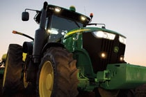 Front view of a 7210R Tractor with planter attachment working in a field