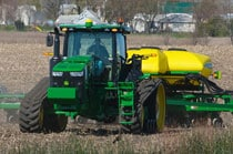 Front view of a farmer driving a 8370RT Tractor with planter attachment down a road