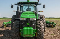Side view of a farmer driving a 8370R Tractor in a field