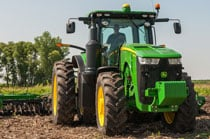 Rear view of a 8320R Tractor with tillage equipment plowing a field