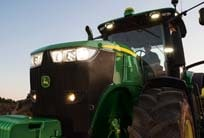 Closeup of a John Deere tractor at dusk with lights on