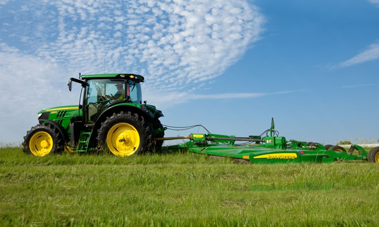 6R Series Tractor with a mowing attachment in a field