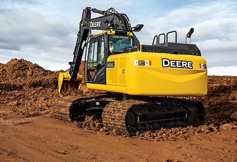 Rear three quarter view of 160G LC Excavator digging dirt