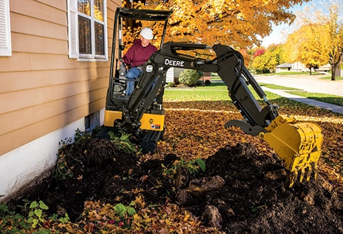Man using 17G compact excavator to dig next to a house foundation
