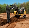 Front view of a 210G LC Excavator digging a trench