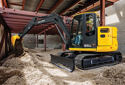 85G Excavator digging in the foundation of a building at a construction site
