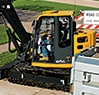 85G Excavator breaking up a road surface in front of a house in a neighborhood