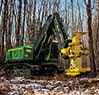 Right front three quarter view of the 903M Tracked Feller Buncher moving in the woods