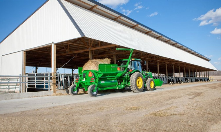 John Deere tractor with attachment unloading a hay bale in front of a farm building