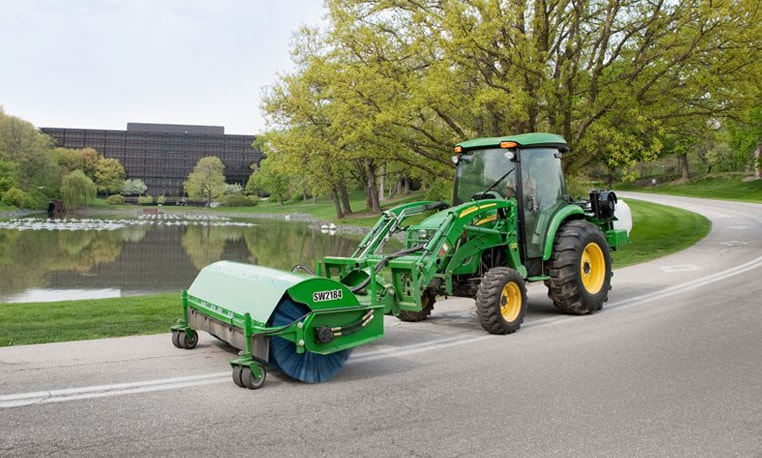 John Deere loader with broom attachment sweeping debris from a road