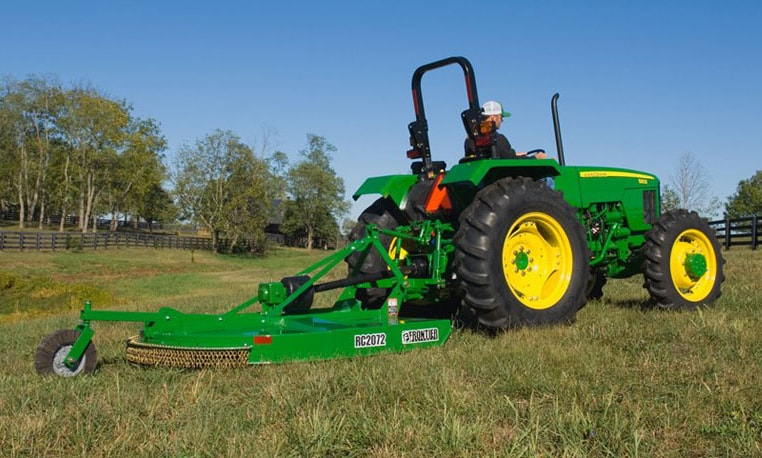 John Deere tractor with rotary cutter attachment trimming grass in a field