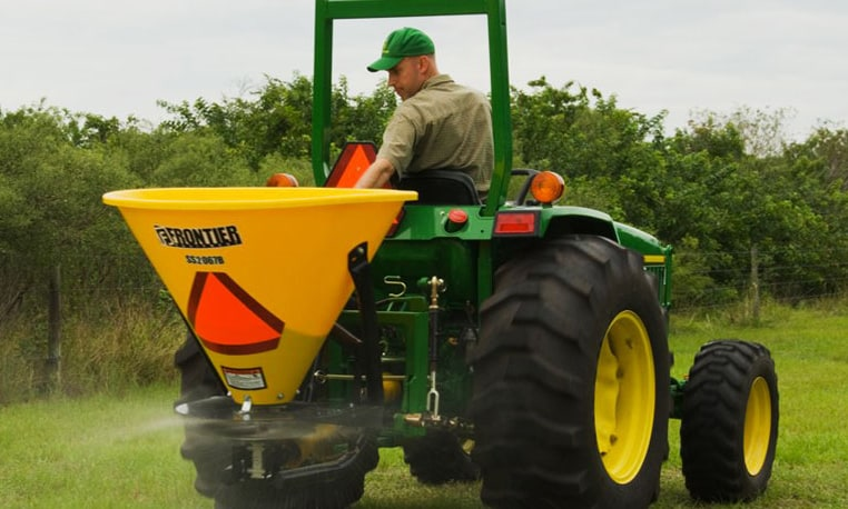 Man using a John Deere tractor with broadcast spreader in a field with green bushes in the background