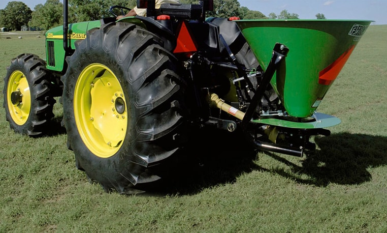 Closeup of a broadcast spreader attached to a John Deere tractor in a grassy field