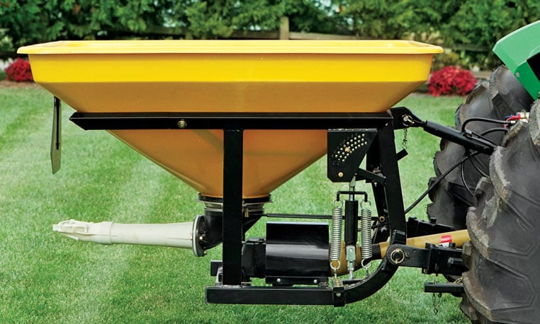 Closeup of a Pendular Spreader on the back of a John Deere tractor with grass and trees in the background