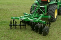 John Deere tractor with DH11 Series Disk Harrows implement in a grassy field